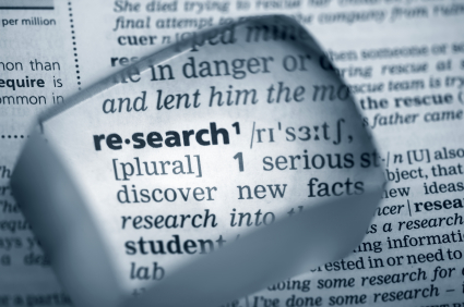 "Magnifying glass highlighting the word ""research"""